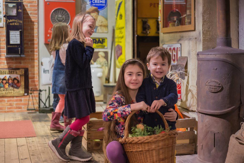 Kinder mit Einkaufskorb in der Ladenzeile