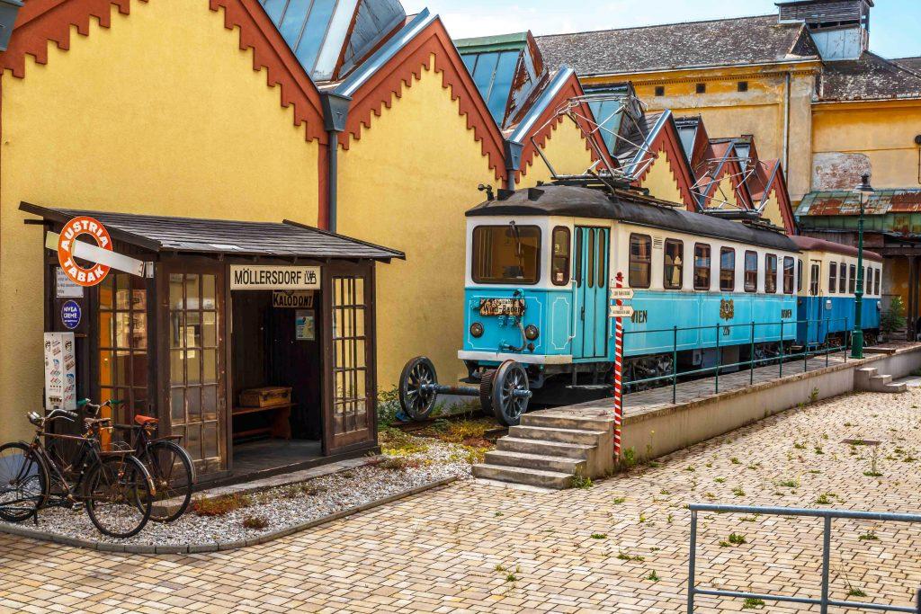Blick ins Freigelände mit Badner Bahn Baujahr 1926 und Haltestelle im Hintergrund die Schedhallen der ehemaligen Kammgarnspinnerei Möllersdorf