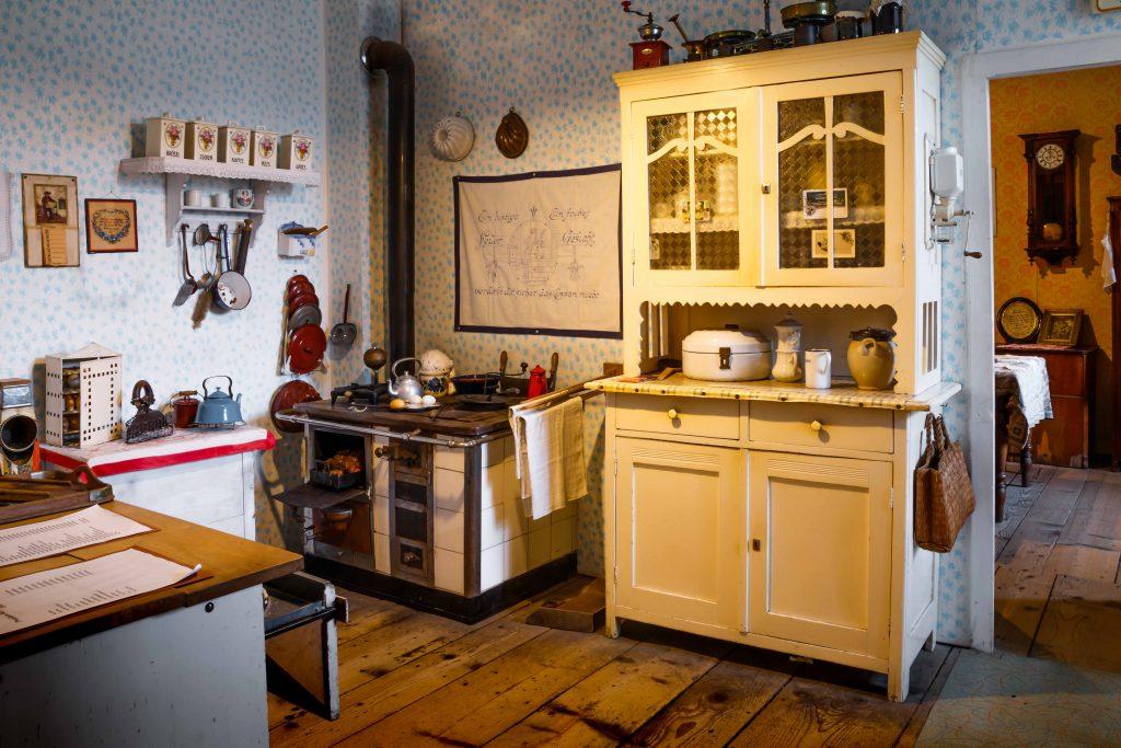 typische Küche in einer Arbeiterwohnung um 1930 mit Kredenz, Herd und Blick ins Wohn/Schlafzimmer