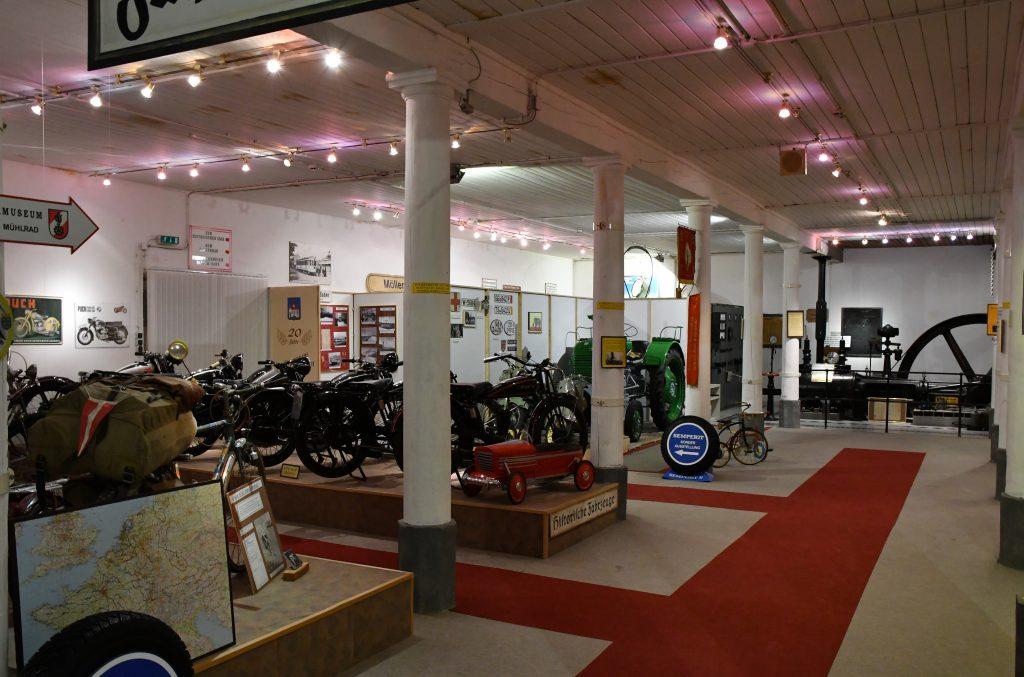 Blick in die Fahrzeughalle mit historischen Motorrädern und der Dampfmaschine