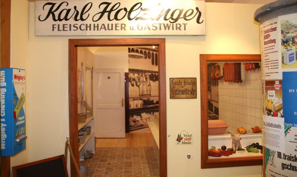 Blick zum Eingang der Fleischerei Holzinger in der Ladenzeile