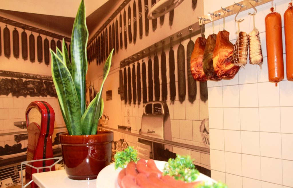 Blick in die Koje der Fleischerei Holzinger mit Wurst und Fleischstücke an der Wand hängend