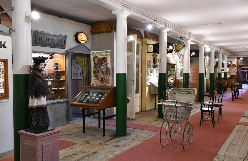 Blick in die Ladenzeile mit einigen Geschäften und einem weißen Kinderwagen im Vordergrund