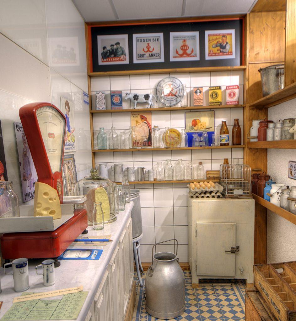 Blick in das Milchgeschäft mit Eiskasten und vielen Milchkannen und Milchflaschen