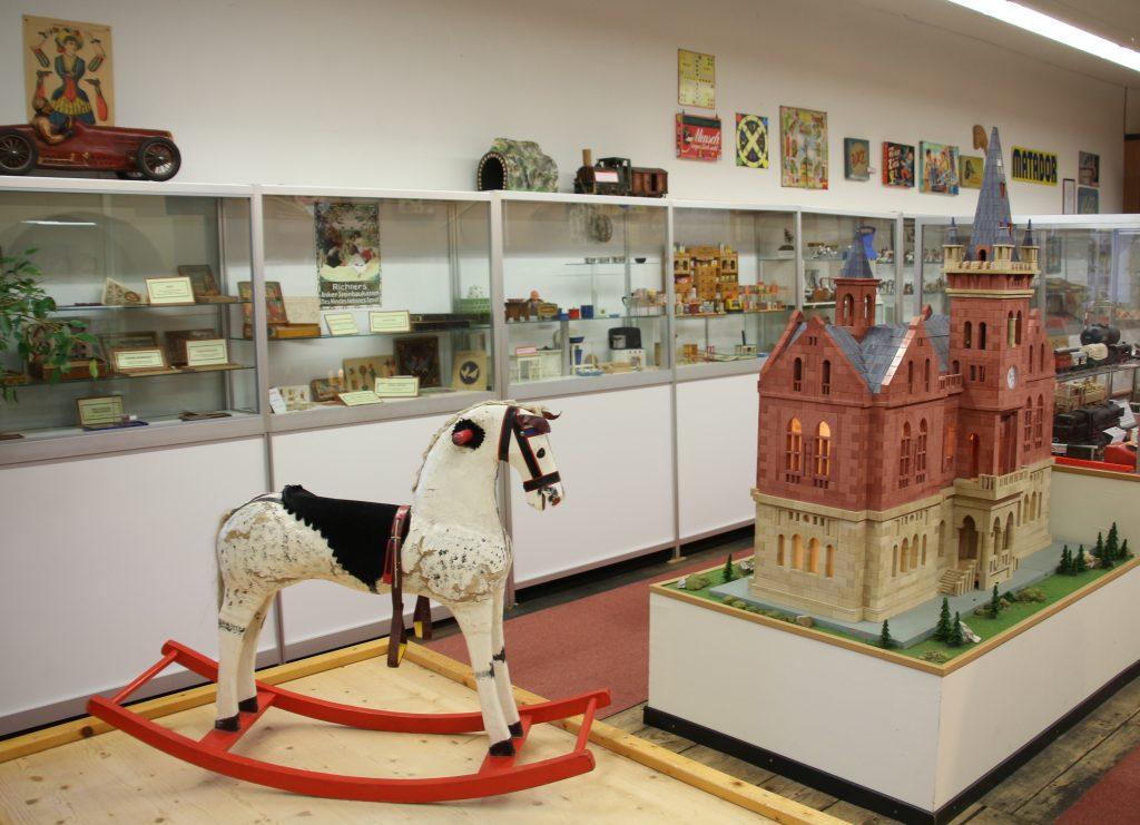 Blick in die Spielzeugsammlung mit Schaukelpferd und Haus aus Ankersteinen